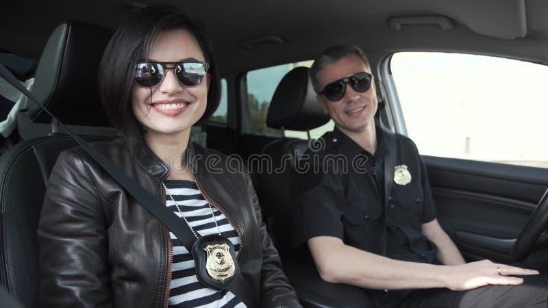 Dos oficiales de policía sonrientes que se sientan en coche fotos de archivo libres de regalías
