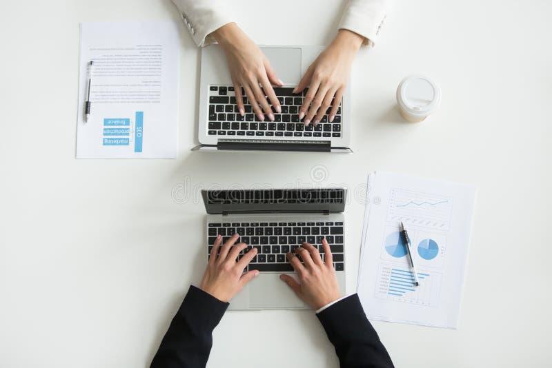 Dos oficinistas que mecanografían en los ordenadores portátiles, opinión ascendente cercana del top fotografía de archivo