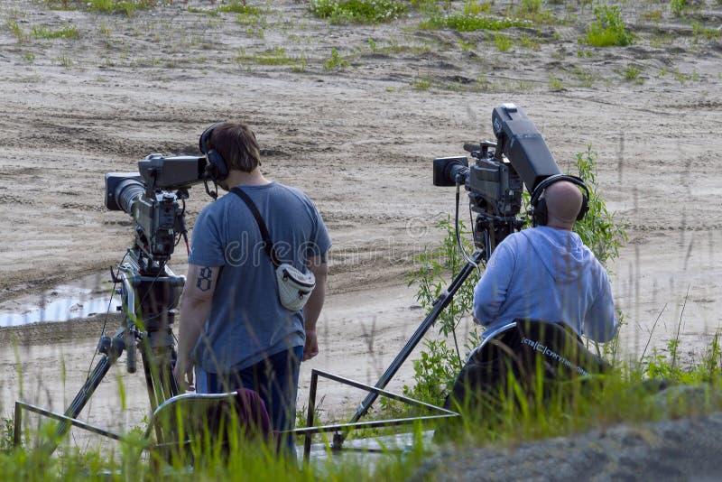 Dos operadores de la cámara de vídeo con los trípodes Visi?n trasera imágenes de archivo libres de regalías