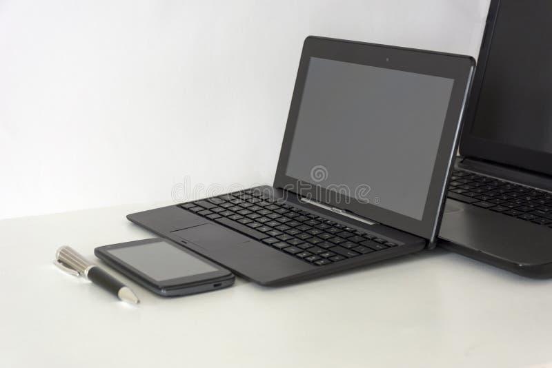 dos, 2 ordenadores portátiles, teléfono móvil, pluma, en una tabla blanca fotos de archivo libres de regalías