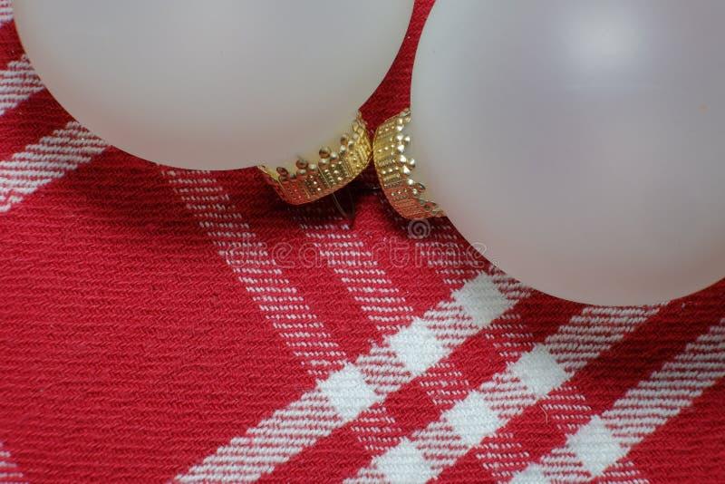 Dos ornamentos blancos opacos de la Navidad del día de fiesta en un rojo y blanco imagenes de archivo