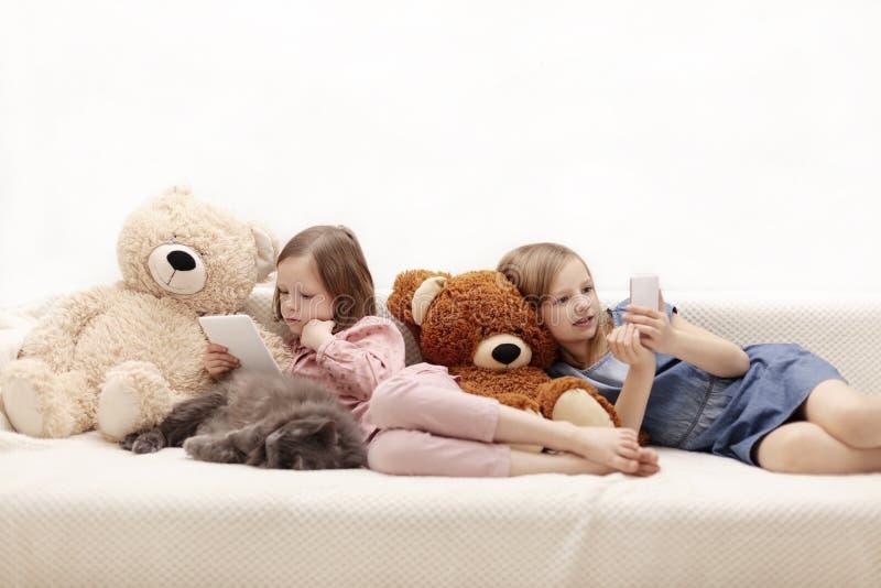 Dos a?os de las hermanas 7 y 8 de las ni?as est?n mirando un eBook y un smartphone en casa en el sof? con su gato fotografía de archivo