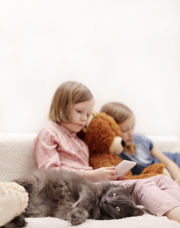 Dos a?os de las hermanas 7 y 8 de las ni?as est?n mirando un eBook y un smartphone en casa en el sof? con su gato imágenes de archivo libres de regalías