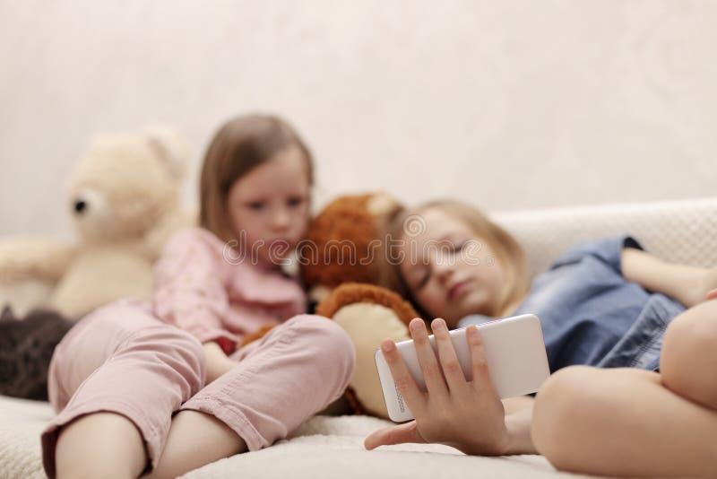 Dos a?os de las hermanas 7 y 8 de las ni?as est?n mirando un eBook y un smartphone en casa en el sof? con su gato imagen de archivo