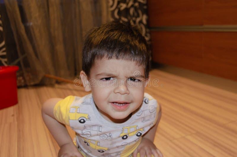 Dos a?os lindos del muchacho que hace caras divertidas el concepto temprano del desarrollo, retrato, expresiones de la cara imagen de archivo