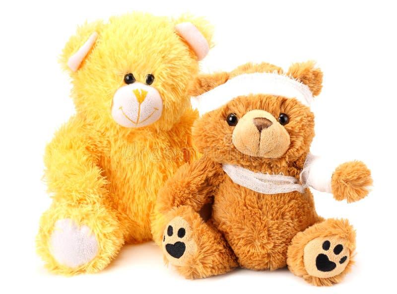 Dos osos de peluche del juguete con el vendaje aislado en el fondo blanco imagen de archivo libre de regalías