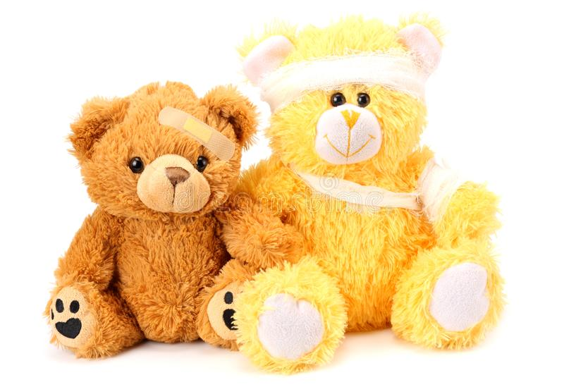 Dos osos de peluche del juguete con el vendaje aislado en el fondo blanco fotos de archivo