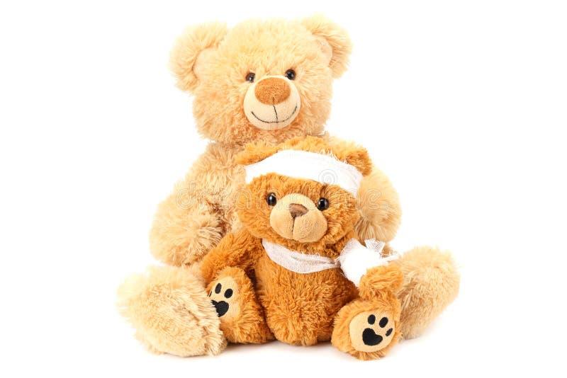 Dos osos de peluche del juguete con el vendaje aislado en el fondo blanco fotos de archivo libres de regalías
