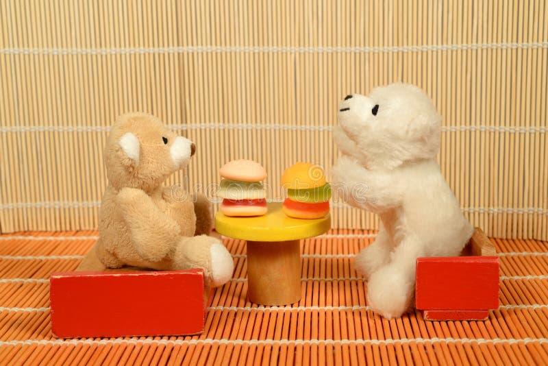 Dos osos de peluche que se sientan delante de dos hamburguesas fotos de archivo
