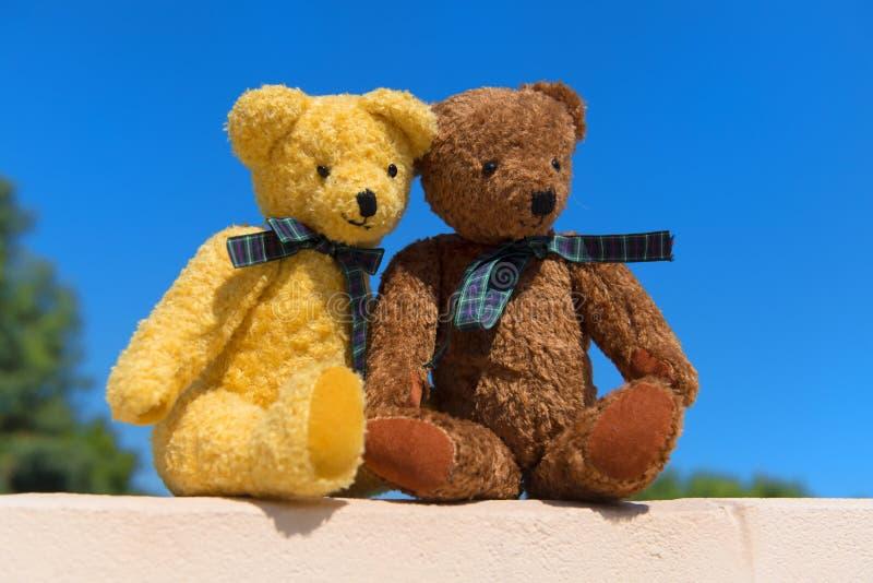 Dos osos del juguete en el amor que se sienta en el ence al aire libre imagenes de archivo