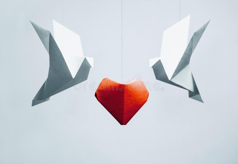 Dos pájaros de la papiroflexia alrededor del corazón de papel rojo fotografía de archivo libre de regalías