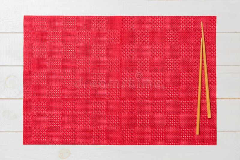Dos palillos del sushi con el mantel rojo vacío, servilleta en la opinión de top de madera blanca del fondo con el espacio de la  fotos de archivo libres de regalías