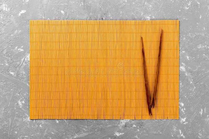 Dos palillos del sushi con la estera de bambú amarilla vacía o la placa de madera en la opinión de top del fondo del cemento con  imagen de archivo libre de regalías
