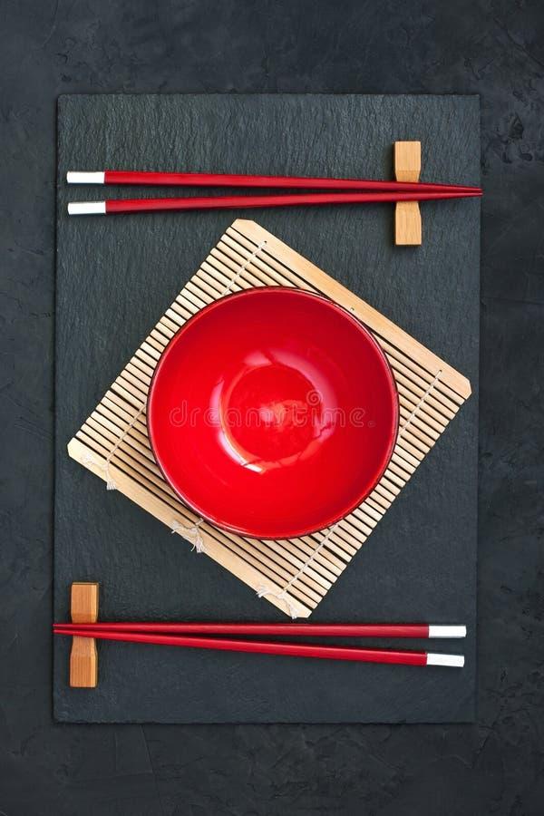 Dos palillos y cuenco rojo Fondo del alimento fotos de archivo libres de regalías