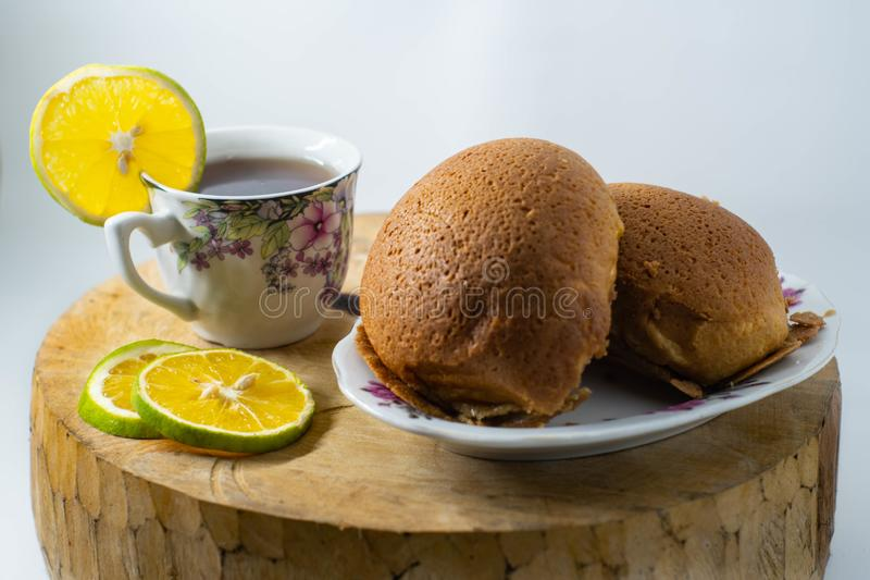Dos panes marrones en una placa y una taza de té caliente del limón se colocan en una estera de madera con un fondo blanco aislad fotos de archivo libres de regalías