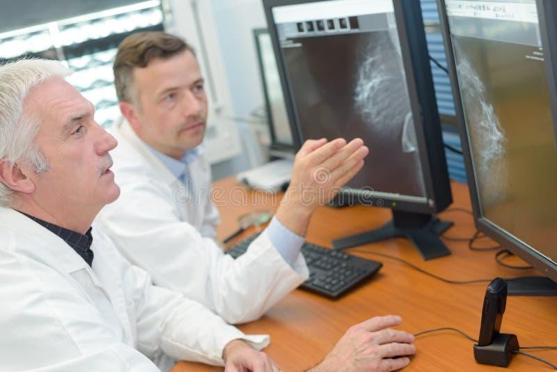 Dos pantallas de ordenador asesores masculinas del personal médico imagen de archivo