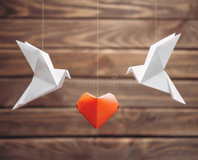 Dos papiroflexia se zambulló los pájaros alrededor de corazón de papel rojo fotografía de archivo