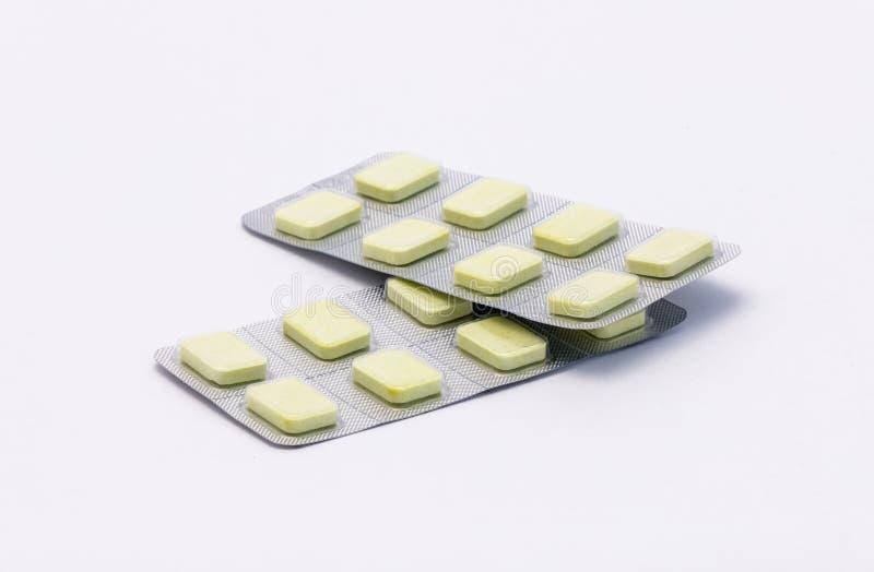 Dos paquetes sellados completos con las tabletas rectangulares blancas mienten en un fondo blanco fotografía de archivo