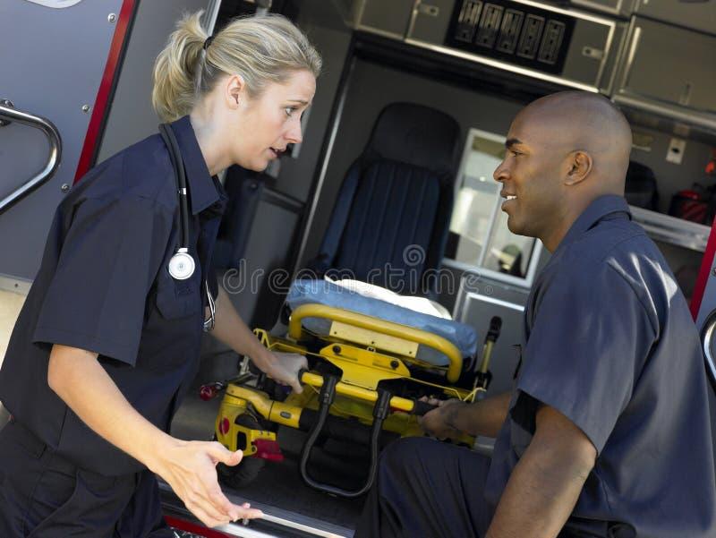Dos paramédicos que quitan la camilla de la ambulancia imágenes de archivo libres de regalías