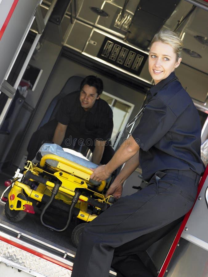 Dos paramédicos que quitan la camilla de la ambulancia imagen de archivo