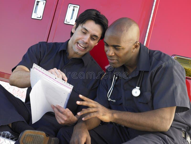 Dos paramédicos que se sientan en su ambulancia fotografía de archivo
