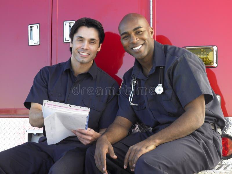 Dos paramédicos que se sientan en su ambulancia foto de archivo libre de regalías