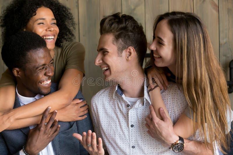 Dos pares africanos y caucásicos felices que abrazan teniendo tog de la diversión imagen de archivo