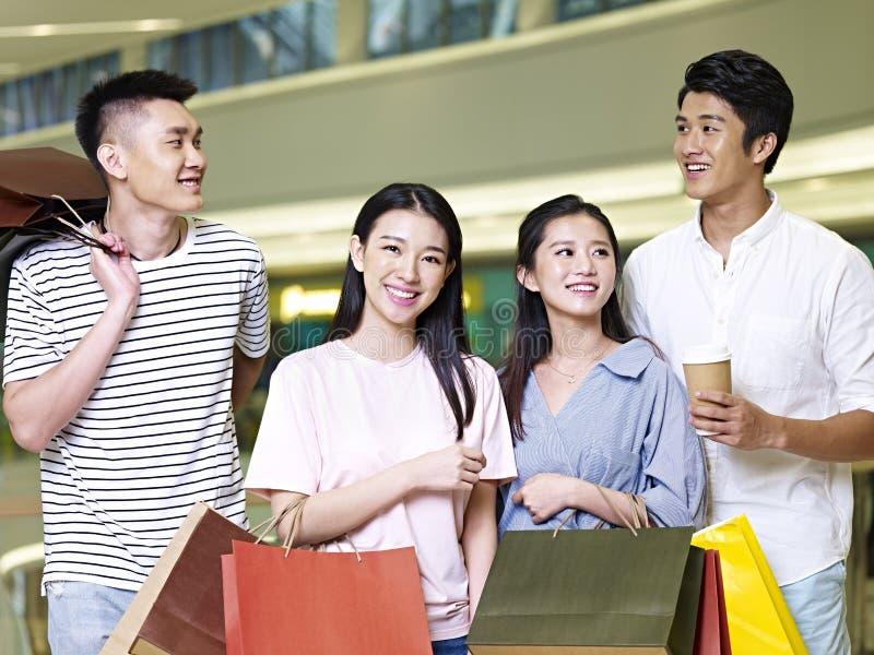 Dos pares asiáticos jovenes en alameda de compras fotografía de archivo
