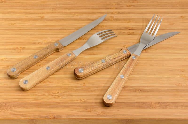 Dos pares de bifurcaciones y de cuchillos con las manijas de madera imágenes de archivo libres de regalías