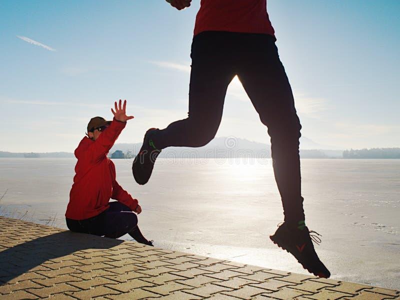 Dos pares de los atletas corridos juntos en paisaje del lago de la primavera imagenes de archivo