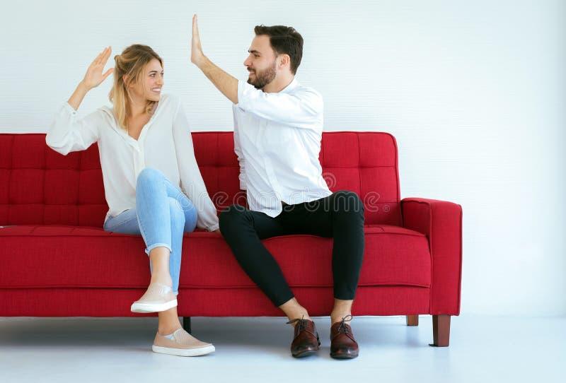 Dos pares do amante de mão do aplauso feliz e o assento no sofá sentimento em casa, povos alegres e atrativos fotos de stock royalty free