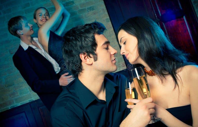 Dos pares felices jovenes en el partido de la celebración o de la noche foto de archivo libre de regalías