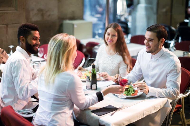 Dos pares felices que se sientan en el restaurante al aire libre imágenes de archivo libres de regalías