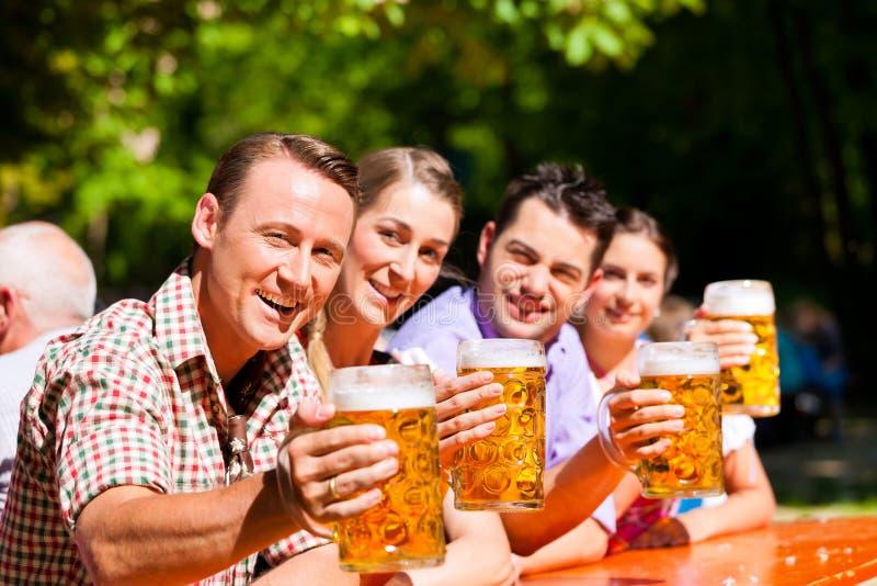 Dos pares felices que se sientan en jardín de la cerveza foto de archivo