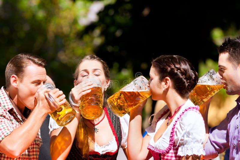 Dos pares felices que se sientan en jardín de la cerveza foto de archivo libre de regalías