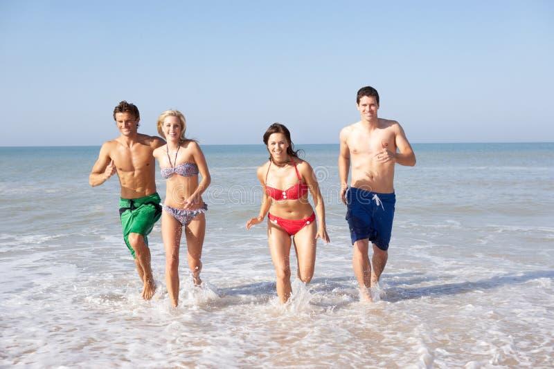 Dos pares jovenes el día de fiesta de la playa imagen de archivo libre de regalías