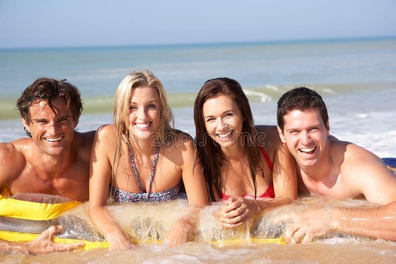 Dos pares jovenes el día de fiesta de la playa imagenes de archivo