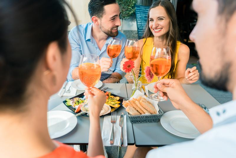 Dos pares jovenes felices que tuestan mientras que se sienta junto en el restaurante foto de archivo libre de regalías