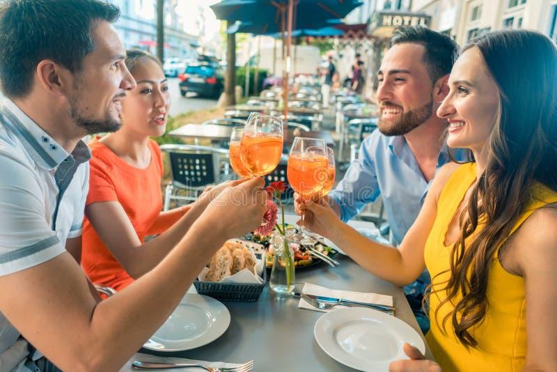 Dos pares jovenes felices que tuestan mientras que se sienta junto en el restaurante imagen de archivo libre de regalías