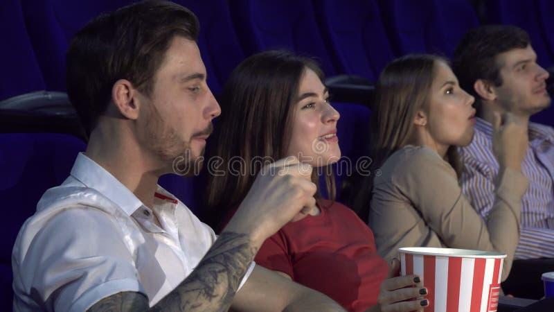 Dos pares jovenes que miran la premier de una nueva película fotos de archivo libres de regalías
