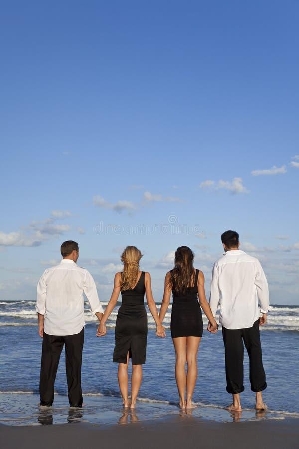 Dos pares, llevando a cabo las manos en una playa fotos de archivo libres de regalías