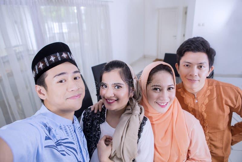 Dos pares musulmanes toman el selfie en comedor foto de archivo