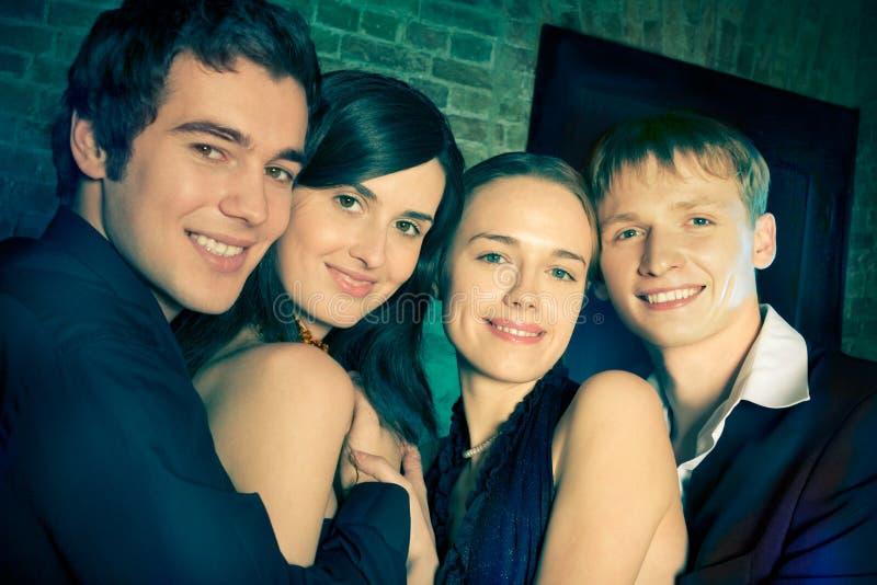 Dos pares o amigos sonrientes jovenes en un partido fotografía de archivo