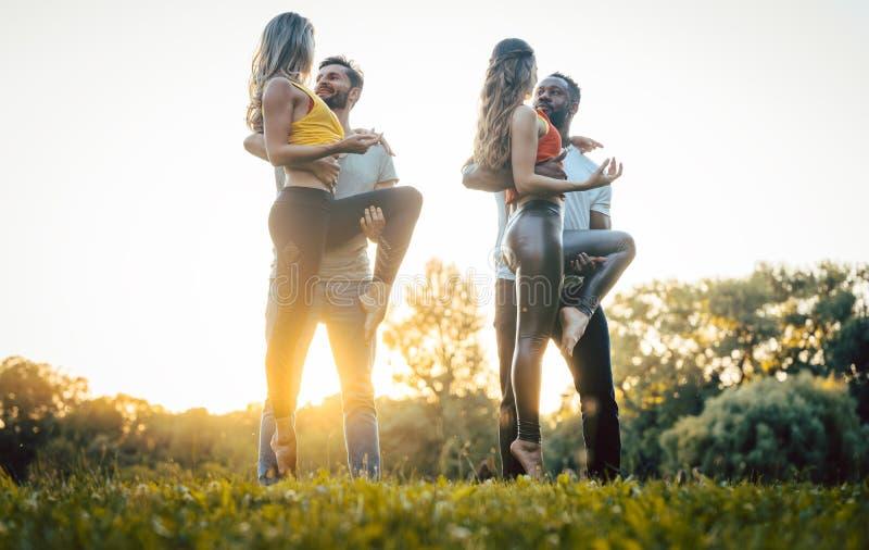 Dos pares que bailan kizomba durante puesta del sol en un parque foto de archivo libre de regalías