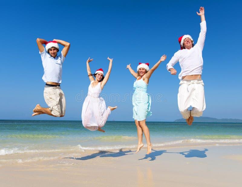 Dos pares que celebran en la playa en la Navidad imagen de archivo