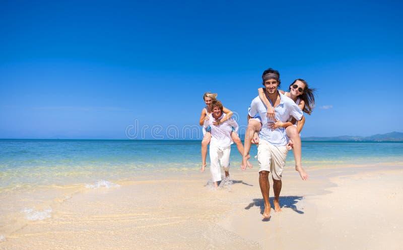 Dos pares que se relajan en la playa imagen de archivo libre de regalías