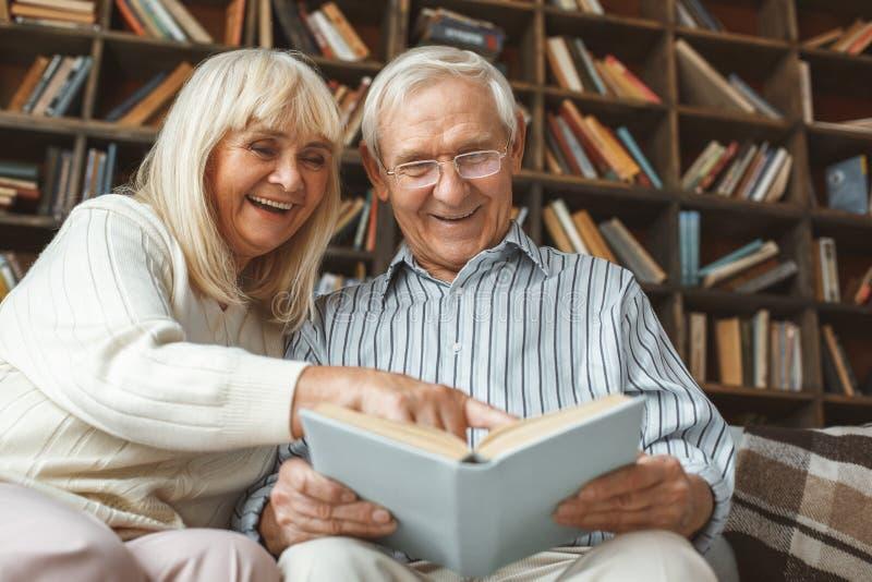 Dos pares riso superior do livro de leitura do conceito da aposentadoria junto em casa foto de stock