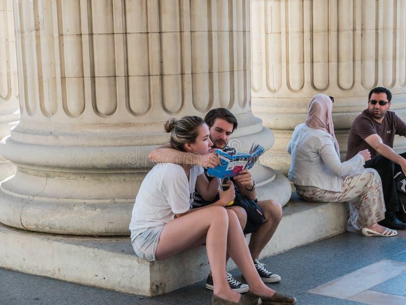 Dos pares se relajan en la base de los pilares del panteón de París fotos de archivo