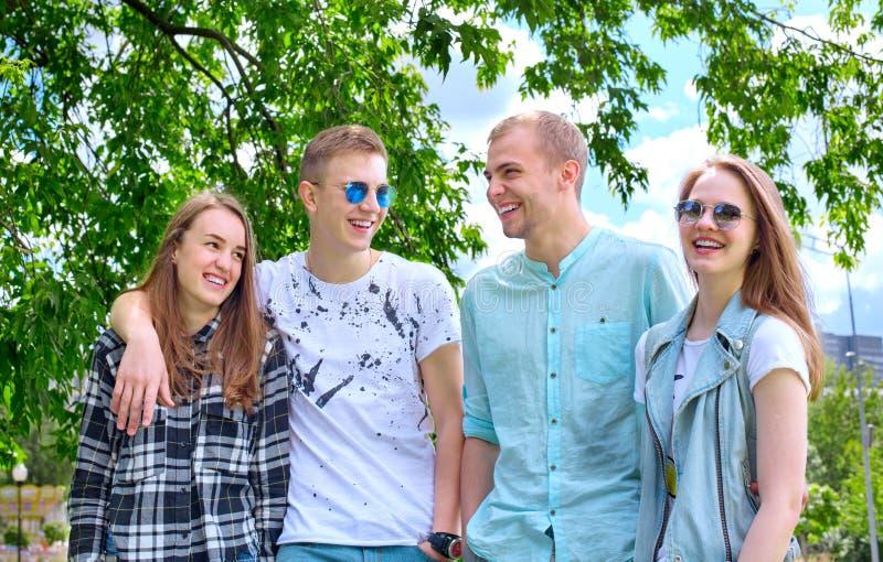 Dos pares sonrientes felices jovenes al aire libre en parque imagen de archivo