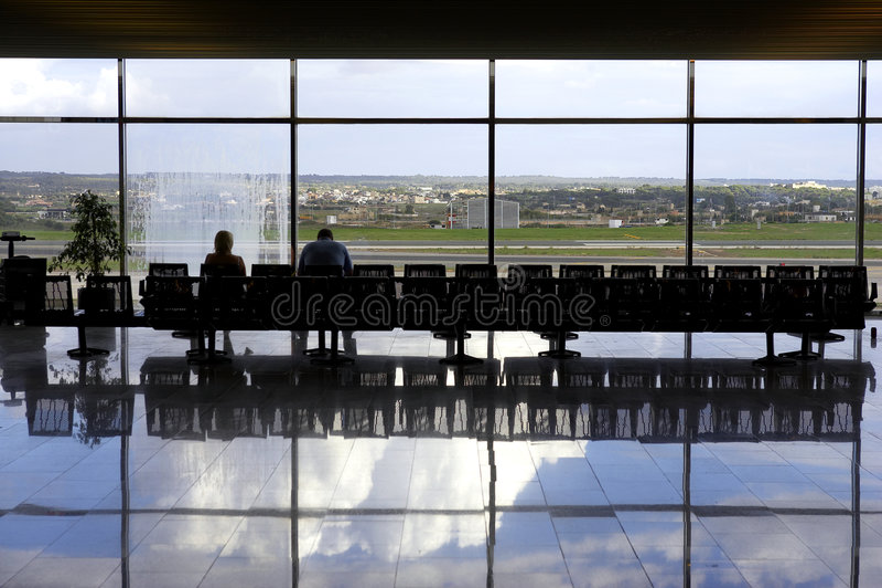 Dos pasajeros que esperan en salón del aeropuerto imágenes de archivo libres de regalías